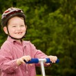 Child with safety helmet riding scooter outdoors — Stock Photo
