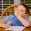 Thoughtful child doing his homework at kitchen table at home — 图库照片