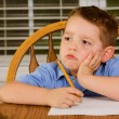 Royalty-Free Stock Photo: Unhappy child doing his homework at kitchen table at home