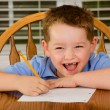 Happy child doing his homework at kitchen table at home — ストック写真