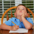 Thoughtful child doing his homework at kitchen table at home — Foto de Stock