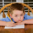 Unhappy child doing his homework at kitchen table at home — Stock Photo