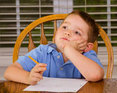 Thoughtful child doing his homework at kitchen table at home — Stok fotoğraf