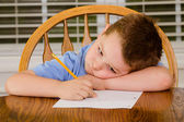 Unhappy child doing his homework at kitchen table at home — 图库照片