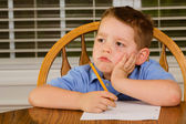 Nieszczęśliwe dziecko robi swoją pracę domową na kuchennym stole w domu — Zdjęcie stockowe