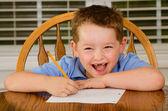 Niño feliz haciendo sus deberes en la mesa de la cocina en casa — Foto de Stock