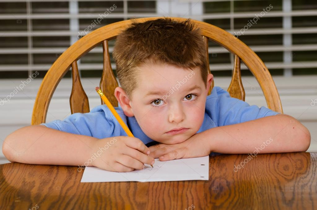 upset boy  Thoughtful child doing his homework at kitchen table at home Alamy
