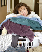 Unhappy, sad, tired woman resting on large, messy pile of laundry — Stock Photo