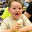 Happy child eating healthy lunch in busy school cafeteria — Stock Photo #25313057