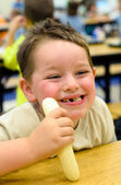 Happy child eating healthy lunch in busy school cafeteria — Stock Photo