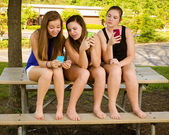 Pre-teen girls texting while hanging out in front of their school — Stock Photo