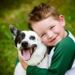 Child lovingly embraces his pet dog, blue heeler — Stock Photo #25462885
