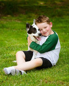 Child lovingly embraces his pet dog, a blue heeler — Stock Photo