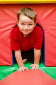 Child crawling through tunnel on play mats — Stock Photo