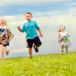 Children having a foot race while running downhill at park - Stock Photo