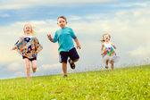 公園で下り坂の実行中に足のレースを持つ子供 — ストック写真