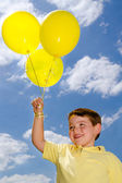 Happy child with balloons on warm, sunny summer day — Stock Photo