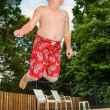 Young child jumping into pool from side — Stock Photo