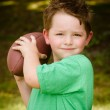 Child playing with football outdoors in yard — Stock Photo