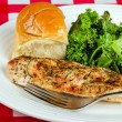 Herb-crusted baked chicken breast with kale and buttered roll — Stock Photo