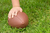 Close up of child's hand on football with room for copy — Stock Photo