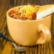Stock Photo: Cup of chili with cornbread and sprinkle of cheddar cheese