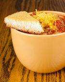 Cup of chili with cornbread and sprinkle of cheddar cheese — Stock Photo