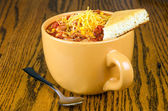 Cup of chili with cornbread and sprinkle of cheddar cheese — Stockfoto