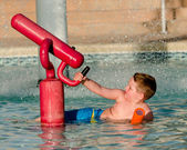 Child playing with water cannon at kiddie pool during summer — Stock Photo