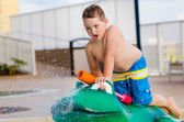 Child playing with water toy at kiddie pool during summer — Stock Photo