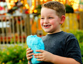 Happy child eating cotton candy at carnival — Stockfoto