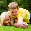 Child tackling mom while playing football together outdoors — Stock Photo #28805923