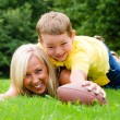 Child tackling mom while playing football together outdoors — Stock Photo #28806027