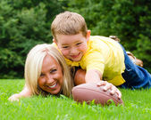 Child tackling mom while playing football together outdoors — Stock Photo