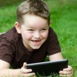 Child using tablet computer outdoors — Stock Photo
