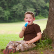 Child eating ice cream treat outdoors on hot summer day — Stock Photo #29006655