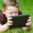 Child using tablet computer outdoors — Stock Photo #29006705