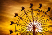 Silhouette of ferris wheel at sunset during summer at county fair — Stock Photo