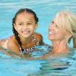 Mother and mixed race girl playing in pool during summer — Stock Photo