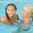 Stock Photo: Mother and mixed race girl playing in pool during summer