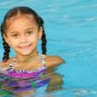 Portrait of happy pretty mixed race child by side of pool during summer — Stock Photo #29335391