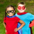 Pretty mixed race girl and Caucasian boy pretending to be superhero — Stock Photo #29335407