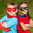 Pretty mixed race girl and Caucasian boy pretending to be superhero — Stock Photo #29335415