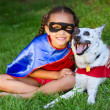Pretty mixed race girl hugging her pet with both dressed up in super hero costumes — Stock Photo