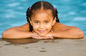 Portrait of happy pretty mixed race child by side of pool during summer — Stock Photo