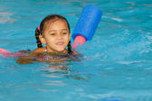 Pretty mixed race child swimming in pool during summer — Stock Photo