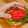 Putting tomato on turkey sandwich — Zdjęcie stockowe