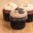 Trio of chocolate and red velvet mini cupcakes with cream cheese frosting — Stock Photo