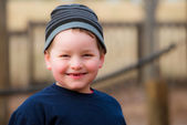 Winter portrait of happy boy playing on playground — Stock Photo