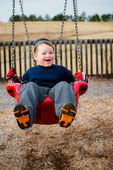 Happy child laughing while swinging at playground — Stock Photo